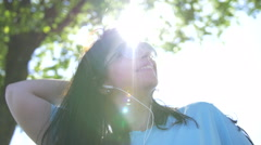 Young woman brushing her hair and listening to music outdoors Stock Footage