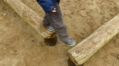 Boy child blonde is engaged in the wooden logs. Little boy playing on the playgr Stock Footage