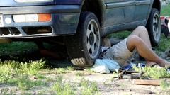 Man working under his car erected on a jack in his court in the country 72 Stock Footage