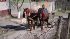 Wagon with two horses go down a street bordered by a fence old twisted wire  Stock Footage