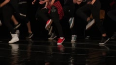 Feet of street dancers evolve on a stage in front of a large audience Stock Footage