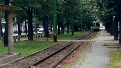 Yellow tram that crosses a verdant park in his way passenger station 61p2 Stock Footage