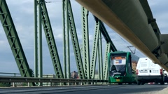 Tram and car traffic on an old iron bridge crossing a big river  Stock Footage