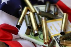 Bullet and money on american flag Stock Photos