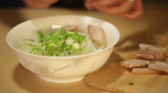 Vietnamese cook puts boiled porck slices into rice noodle bowl using chopstic Stock Footage