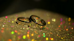 Two wedding rings on a colorful shining background. Stock Footage
