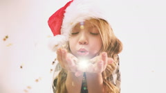 Pretty girl with Christmas cap blows golden stars from theirs hand Stock Footage