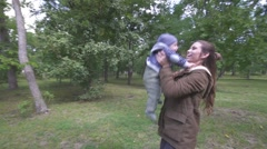 Mother with her child playing in autumn park Stock Footage