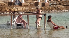Israel.Dead Sea.A group of people sitting in the Dead Sea. Stock Footage