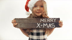Pretty girl with Christmas cap holds wooden board with merry x-mas Stock Footage