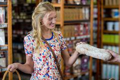 Smiling woman purchasing a loaf of bread Stock Photos