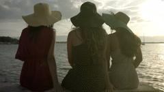 Beautiful girls in hats sitting on the beach,  enjoying a summer sunrise Stock Footage