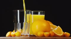 Pouring orange juice into glass slow motion HD video. Still life citrus on black Stock Footage