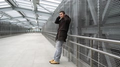 Young man stands in pedestrian overpass, looks around and waiting for someone Stock Footage