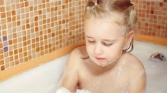 Little girl having fun in a bathtub full of soap foam Stock Footage