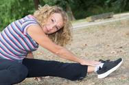 Senior woman in fitness outfit relaxing in park Stock Photos