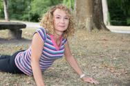 Athletic mature girl doing yoga outside- crocodile pose Stock Photos