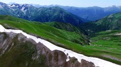 Aerial view mountain valley 4k nature video. Green rocky landscape, snow range Stock Footage