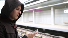 Young man waiting train in a subway station and using mobile phone Stock Footage