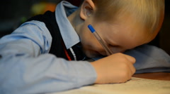 Boy 7 years  his homework at his desk Stock Footage