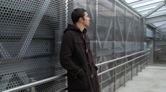 Young man stands in a subway, looks around and waiting for someone Stock Footage