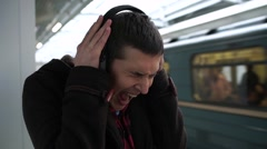 Young man with noise blocking safety acoustic earmuffs grimacing from loud Stock Footage