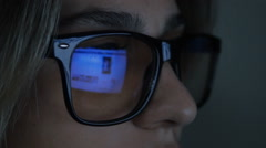 Closeup shot of woman in glasses surfing internet, at night Stock Footage