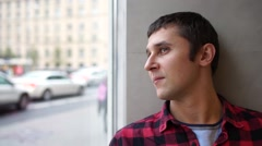 Young man looks out the window to the street where people are passing and Stock Footage
