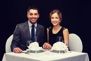 Smiling couple holding hands at restaurant Stock Photos