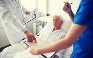 Doctor and nurse visiting senior woman at hospital Stock Photos