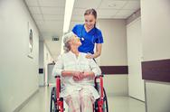 Nurse with senior woman in wheelchair at hospital Stock Photos