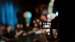 Closeup view of a girl filming a dancer on her camera. Blurred dancing man on Stock Footage
