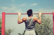 Young man exercising on horizontal bar outdoors Stock Photos