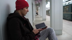 Young man reads e-book and waiting train in a subway station. Train arrives, he Stock Footage