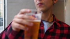 Young man drinking beer from plastic cup indoor and looking out window into Stock Footage