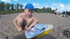 Boy with blond hair launches radio-controlled boat on the river Stock Footage