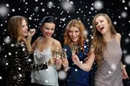 Happy women clinking champagne glasses over snow Stock Photos