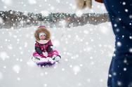 Parent carrying happy little kid on sled in winter Stock Photos