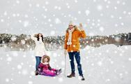 Happy family with sled walking in winter outdoors Stock Photos