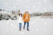 Happy couple walking along snowy winter field Stock Photos