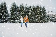 Happy couple running in winter snow Stock Photos