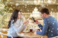 Couple with smartphones drinking tea at cafe Stock Photos