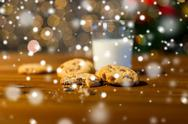 Close up of cookies and milk over christmas lights Stock Photos
