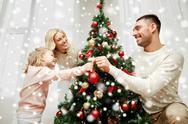 Happy family decorating christmas tree at home Stock Photos