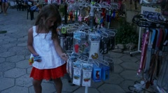 Little girl is choosing anything in street market. Little shopper Stock Footage