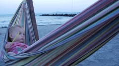 Baby girl is swinging in hammock on the sandy beach Stock Footage