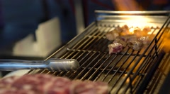 4k Vendor cooking a beef meat bits with blowtorch on grill in Night market-Dan Stock Footage