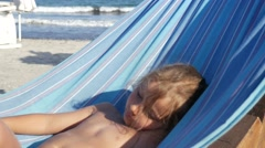 Little girl is swinging in hammock on the sandy beach Stock Footage