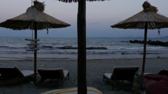 Beach on evening time. Parasols and sun beds. No people Stock Footage