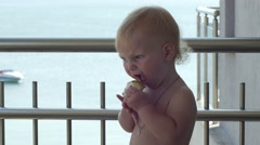 Baby eating an apple on balcony. Kid is eating an apple. Stock Footage
